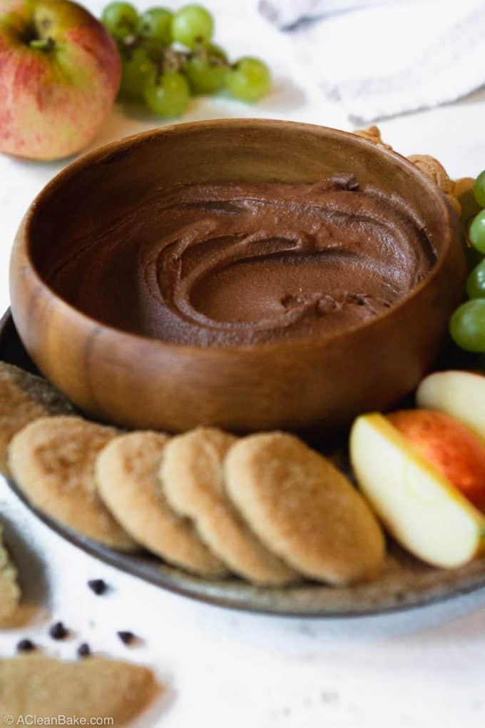 Bowl of chocolate dessert hummus on plate with cookies and fruit