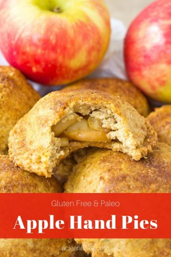 Paleo Apple Hand pie with bite taken out of it sitting on a pile of whole paleo apple hand pies