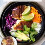 healthy chunks of fish in a bowl with cilantro, purple cabbage, lime, and lettuce
