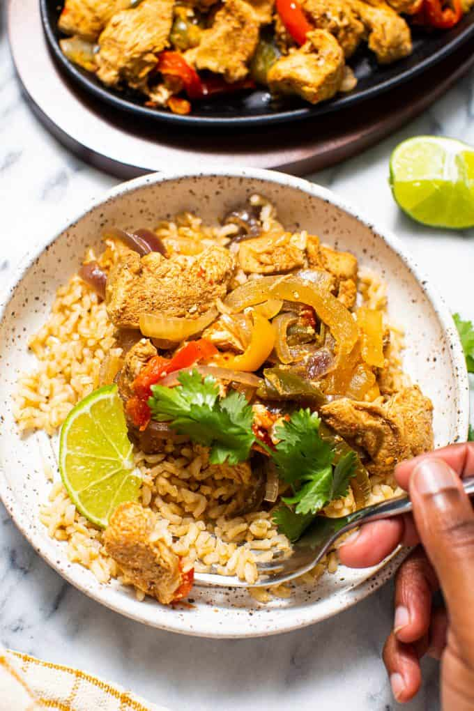 Bowl of slow cooker/crockpot chicken fajitas over rice with a hand holding a fork
