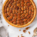 A round pie shell is seen from the top down view with pecans placed in a uniform swirl pattern into the center.