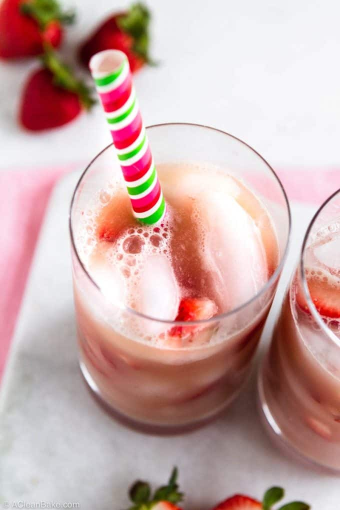 Homemade pink drink recipe in a glass with strawberry slices and a straw