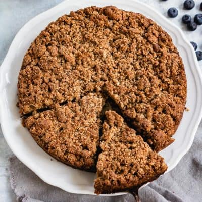 Paleo blueberry crumb cake on a plate with a spatula pulling a slice out