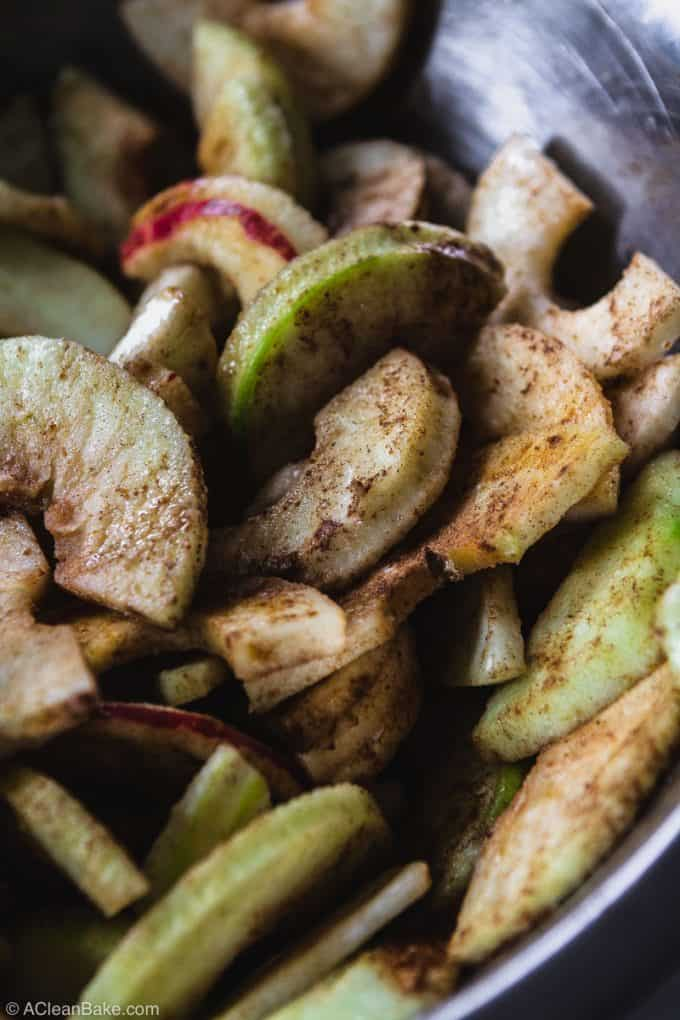 Peeled and sliced apples covered in cinnamon for vegan paleo apple crisp