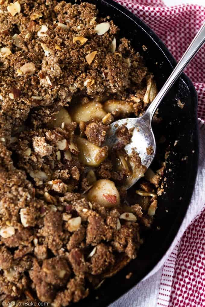 Batch of vegan paleo apple crisp in a pan with a spoonful removed