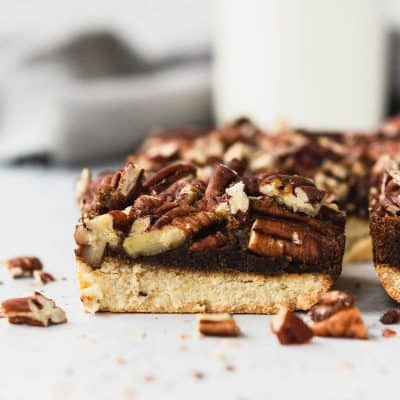 gluten free and paleo pecan pie bar on a table with a glass of milk