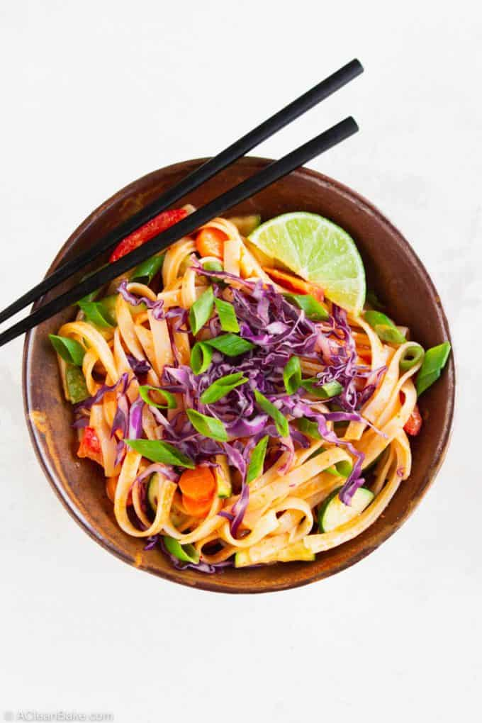 gluten free curry noodles in a bowl topped with a lime wedge, shredded red cabbage, and sliced scallions