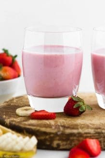 Strawberry Banana Smoothie with Added Protein in a cup sitting on a cutting board surrounded by fruit