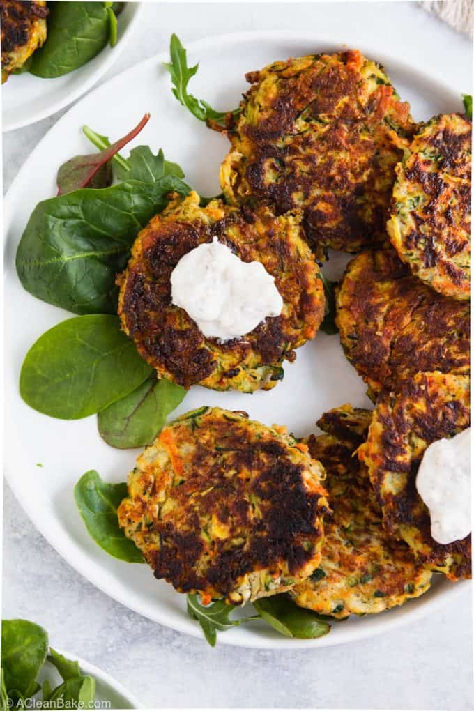 Paleo gluten free vegetable fritter with yogurt sauce on a plate