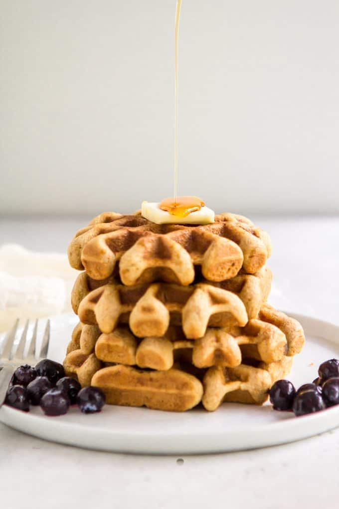 Stack of paleo gluten free waffles on a plate with a drizzle of syrup hitting the top