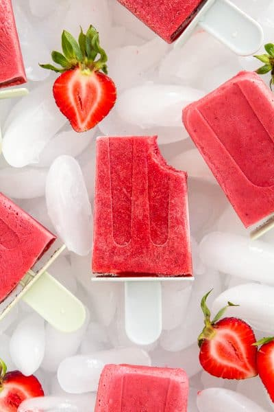 Tray of Strawberries and Cream Popsicles (gluten free, paleo, vegan, and naturally sweetened) with ice and fresh strawberries