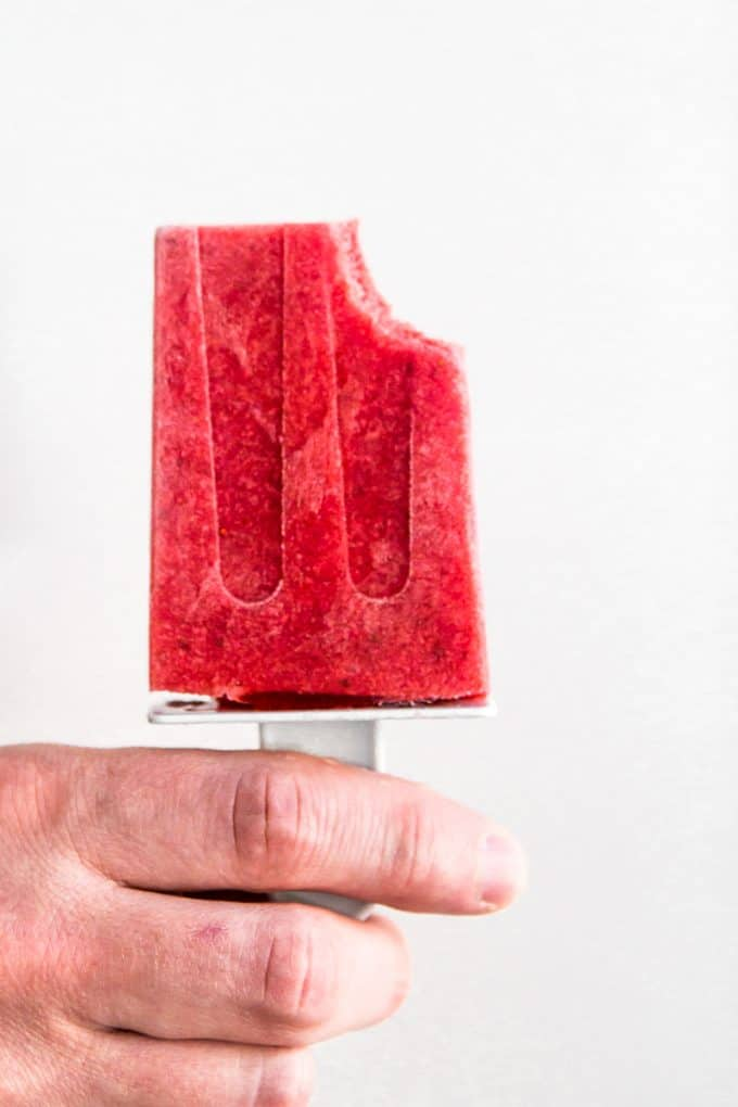 Hand holding a Strawberries and Cream Popsicle (gluten free, paleo, vegan, and naturally sweetened)