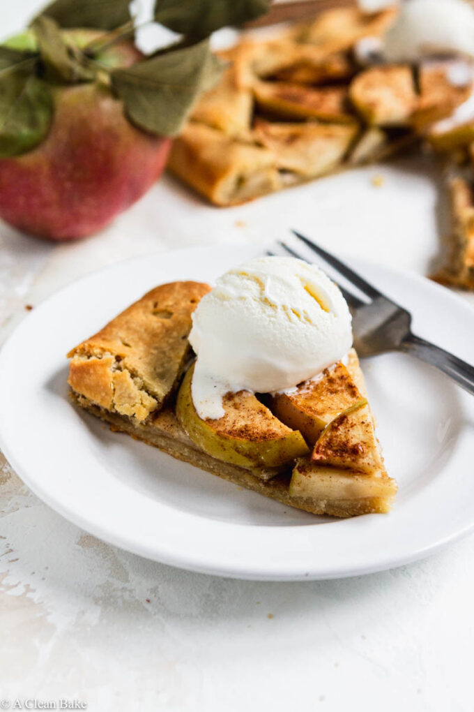Slice of paleo gluten free apple galette on a plate topped with ice cream and apples in the background