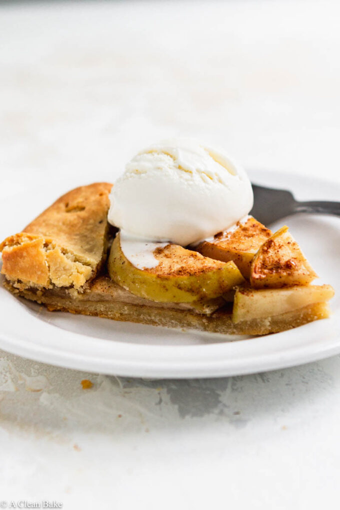 Slice of paleo gluten free apple galette on a plate topped with ice cream on a white backgound