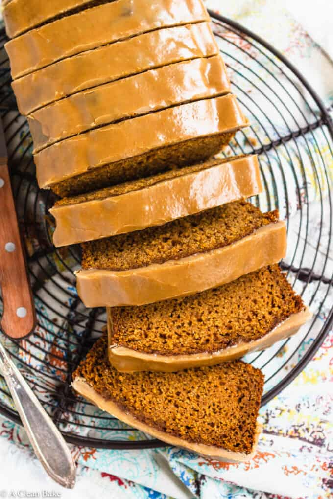 Sliced pumpkin bread with maple glaze on a cooling rack
