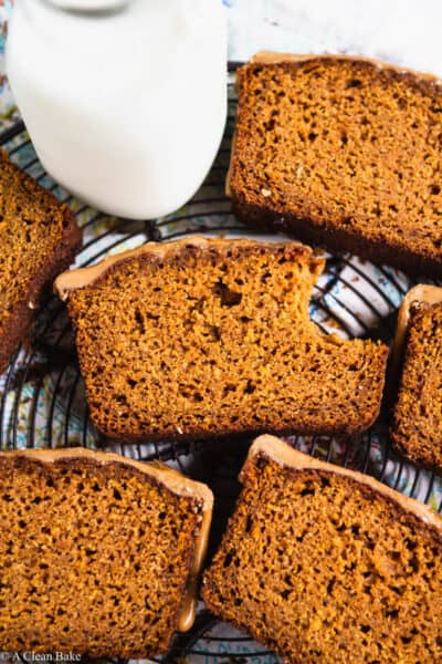 Slices of paleo gluten free pumpkin bread on a cooling rack with a glass of milk
