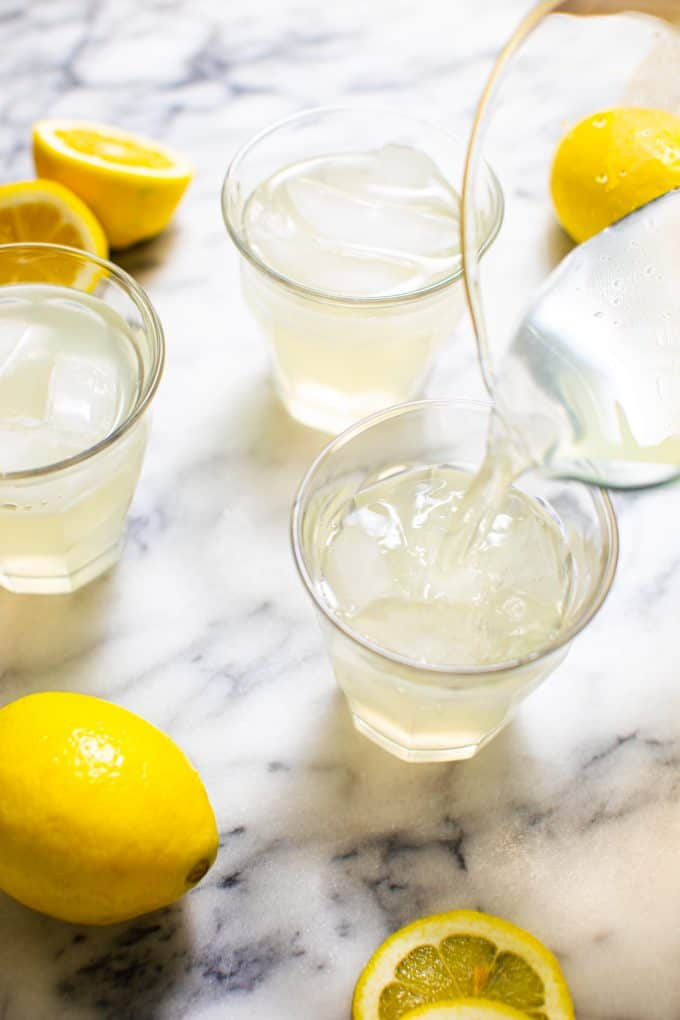 Glass of Sugar Free Lemonade surrounded by lemons on a marble table