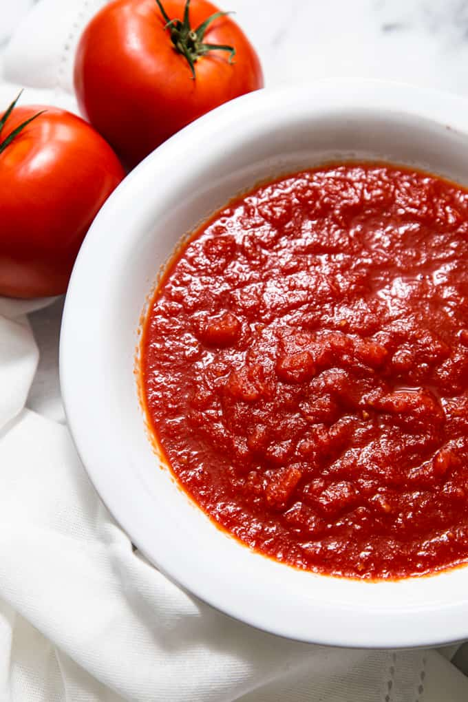 Close up of pizza sauce in a white bowl