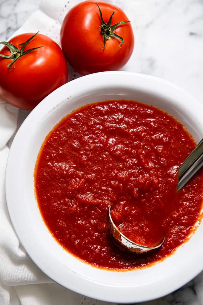 Bowl of simple pizza sauce with a ladle in it