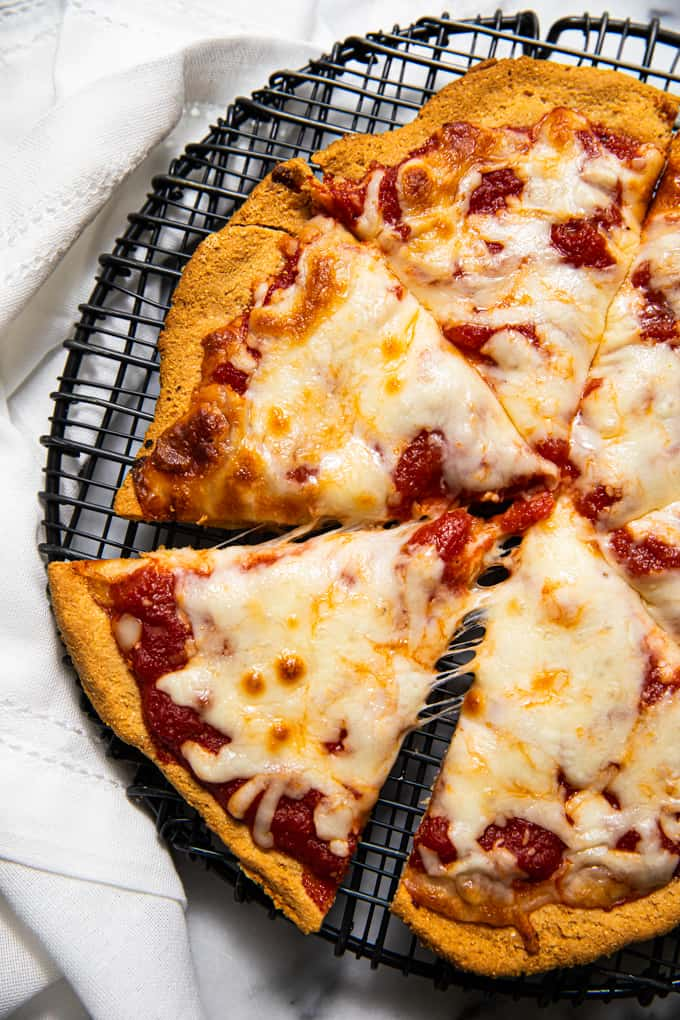 Sliced gluten free paleo pizza crust topped with sauce and cheese