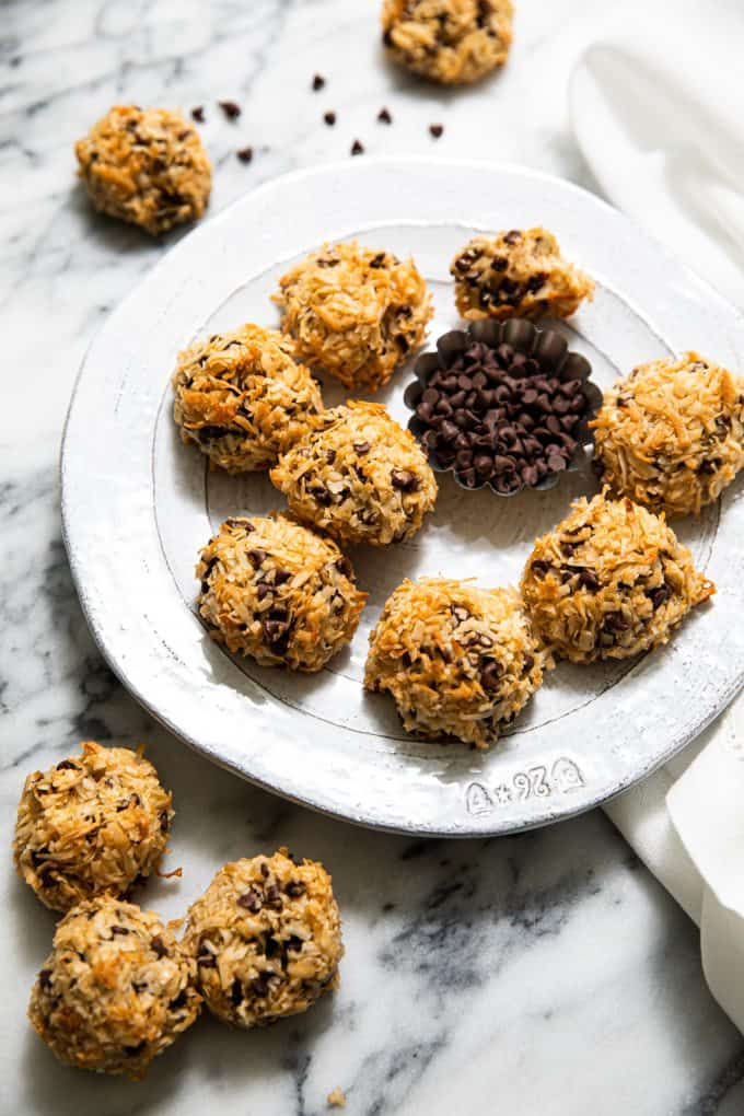 Chocolate Chip Coconut Macaroons on a platter scattered across a marble table