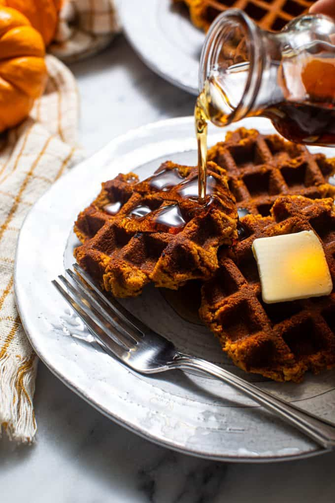 PIle of Paleo and Gluten Free Pumpkin Waffles on a plate with butter and syrup and a fork