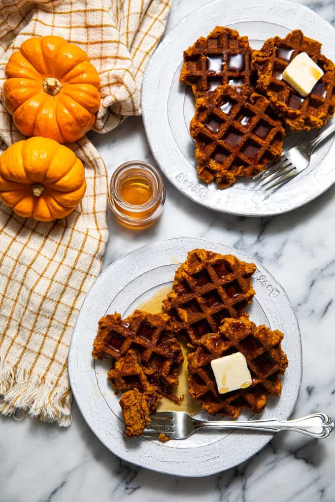 Two plates of Paleo and Gluten Free Pumpkin Waffles with butter and syrup and a fork