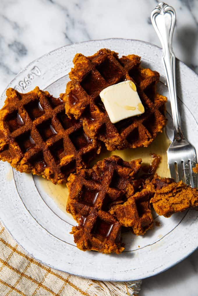 Plate of Paleo and Gluten Free Pumpkin Waffles with butter and a bite taken out of one of the waffles, with another bite on a fork