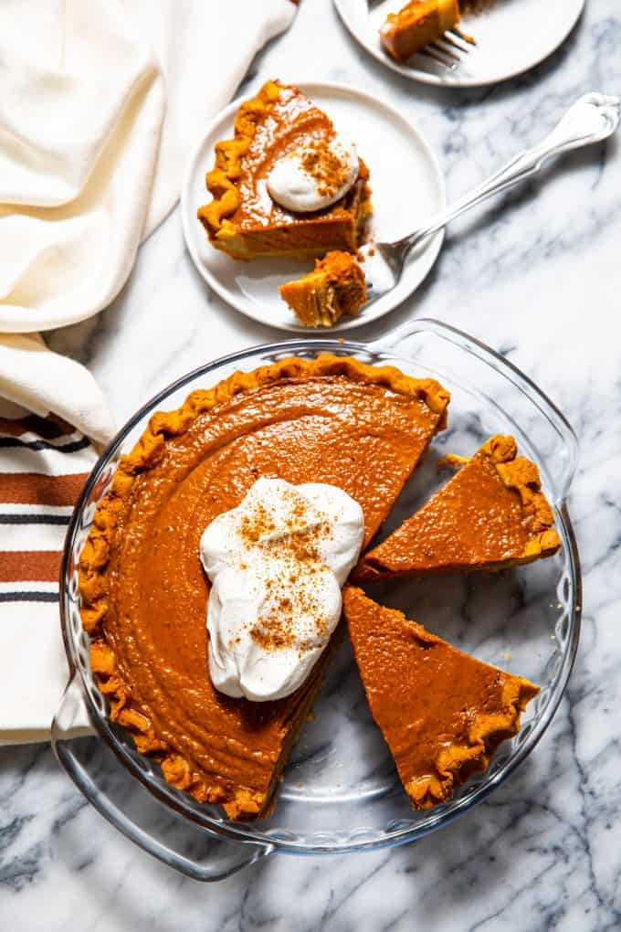 Paleo gluten free pumpkin pie from above topped with whipped cream, and a slice next to it on a plate