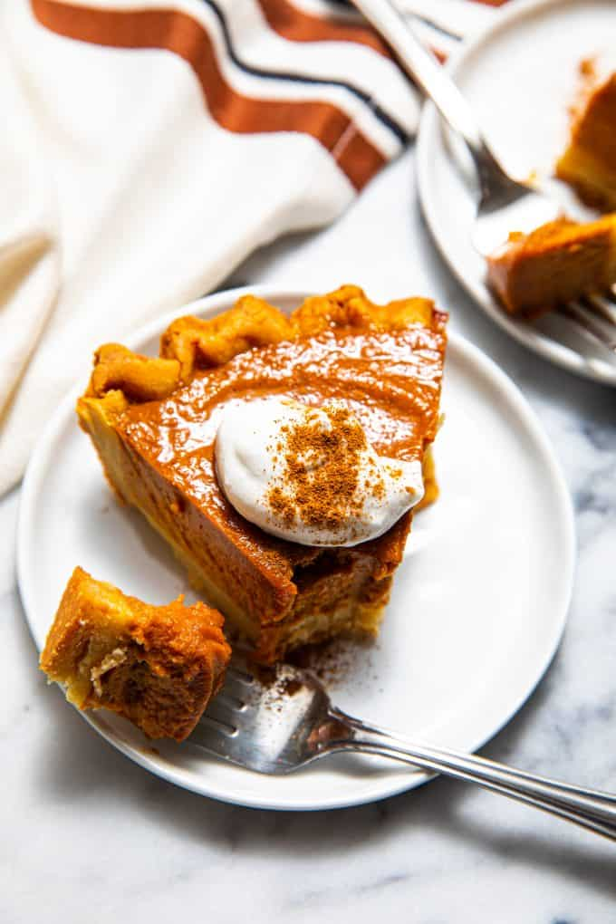 Slice of paleo gluten free pumpkin pie on a plate with a fork