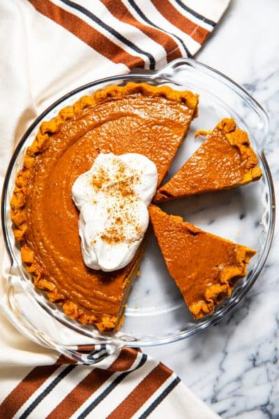 Paleo gluten free pumpkin pie from above topped with whipped cream, and a few slices cut out