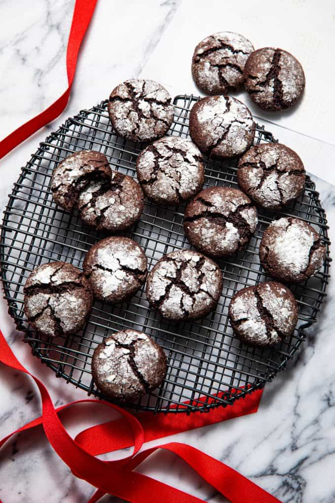 Array of Paleo gluten free chocolate crinkle cookies spilling off of a round wire rack with a red ribbon